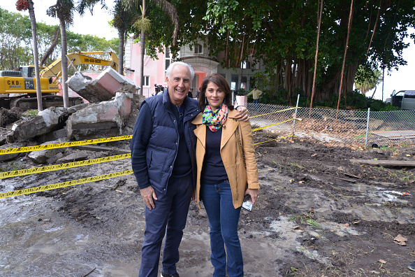 Fast food magnate Christian de Berdouare and his wife Jennifer Valoppi pose in front of the property that they now own and which was formerly the Miami Beach home of the late Colombian drug lord Pablo Escobar as it is demolished on January 19, 2016 in Miami Beach, Florida.