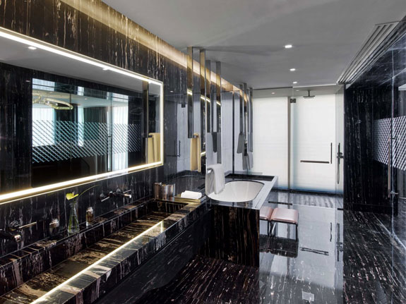 the-bathroom-is-certifiably-huge-with-floors-and-ceilings-covered-in-marble-book-matched-slabs-to-create-a-dramatic-pattern-they-surround-a-gigantic-sink