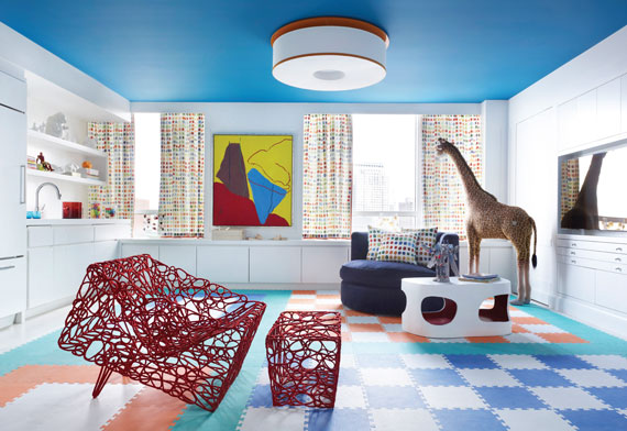 A large playroom designed by Sandra Nunnerley features artwork by Raymond Parker, a red chair and ottoman designed by Cheick Diallo and a table by Jacques Jarrige.