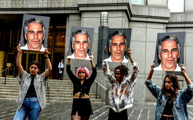 A protest group holds up signs of Jeffrey Epstein (Credit: Getty Images)